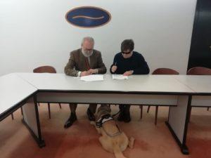 De izquierda a derecha: Mariano Gómez-Ulla, Presidente del Club Financiero Atlántico y Enrique Varela, Presidente de funteso. Sentados los dos firmando el convenio. A sus pies, en medio de ambos, Balú, el perro-guía de Enrique Varela
