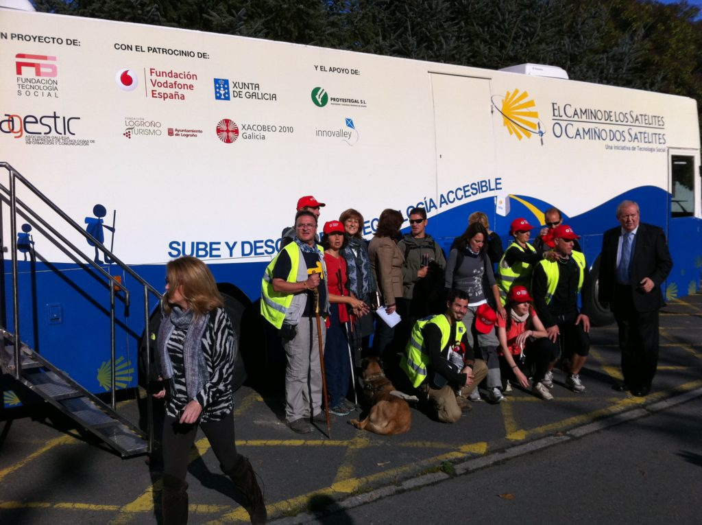 Los peregrinos llegan a Santiago y se colocan para foto en grupo delante del autobús que alojó la exposición tecnológica itinerante.