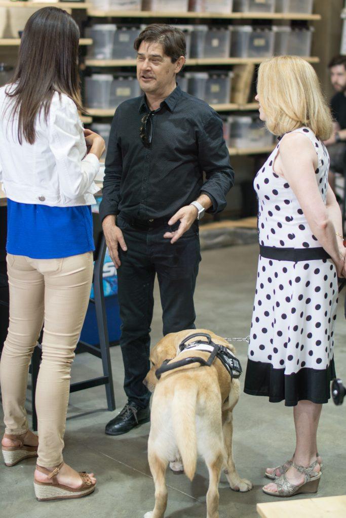 Marta Portero, de espaldas y a la izquierda, y enrique Varela, a la derecha, hablando sobre la entrevista. A los pies de Enrique, Balú, su perro guía. Y ás a la derecha, en la escena, Celia Romero.